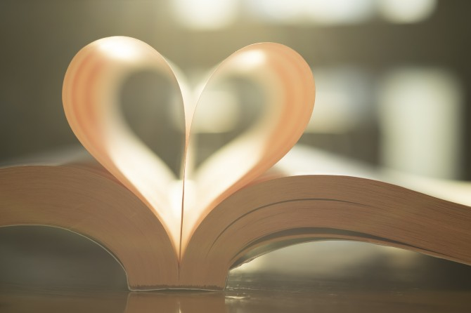 Soft heart shape from paper book page. Warm vintage color of sun