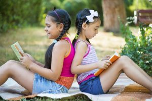Hispanic sisters reading book in summer park