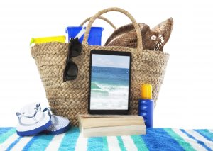 """Digital tablet, books and other accessories for the beach. The image on the tablet is the photographer's own."""