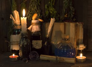 Vintage still life with healing herbs, glass bottles with remedies, manuscripts and open book