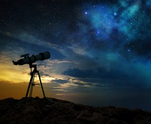 milky way at dawn and silhouette of a telescope