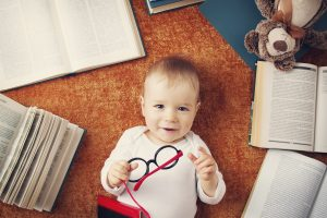 One year old baby among books with spectackles and a teddy bear