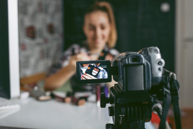 Smiling Teenage girl making her video blog about makeup. She is using home video camera to record video blogs and publish online. Selective focus to camera screen. She is blogger and vlogger.