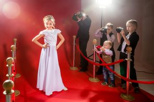 Beautiful little girl in a long evening gown is posing for photographers on a red carpet illuminated by spotlights