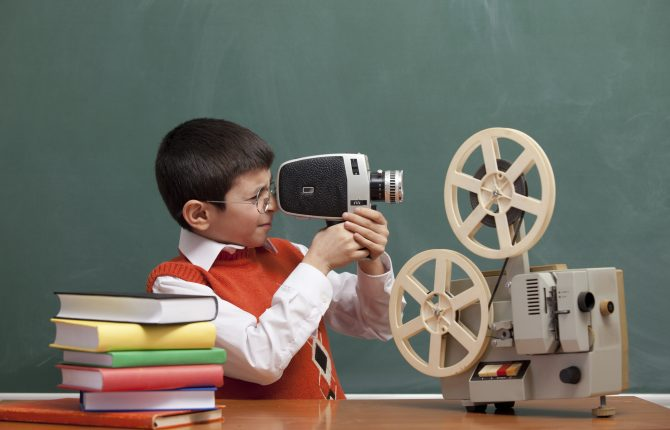Little wearing orange waist and shirt looking through viewfinder of video camera in front of blackboard.Old fashioned film projector and stack of books on table.The image was shot with a full frame DSLR camera in horizontal composition.