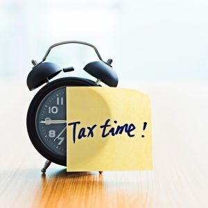 Tax Time sticky note on alarm clock.