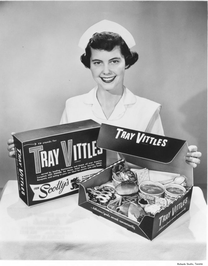 Image of a woman displaying box of takeout food