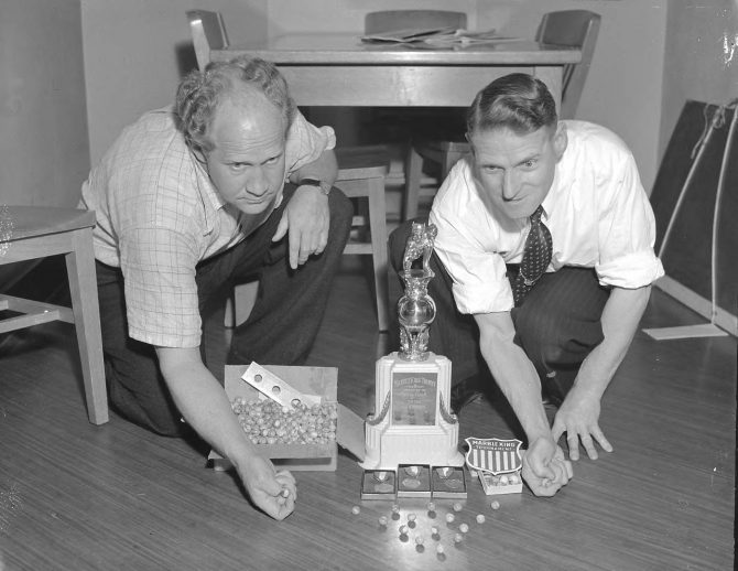 Image of two men playing marbles