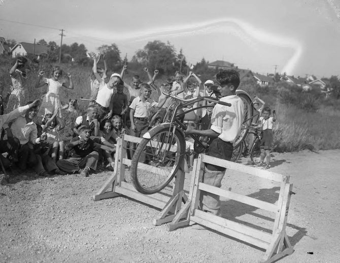 Image of a boy with a bicycle on an obstacle course