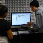 Older boy helping a girl in Digital Media Lab