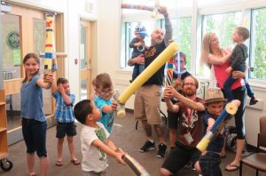 Image of dads and kids playing with pool noodle lightsabers at Daddy Boot Camp