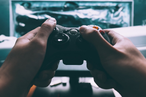 Hands holding an Xbox controller and playing a video game