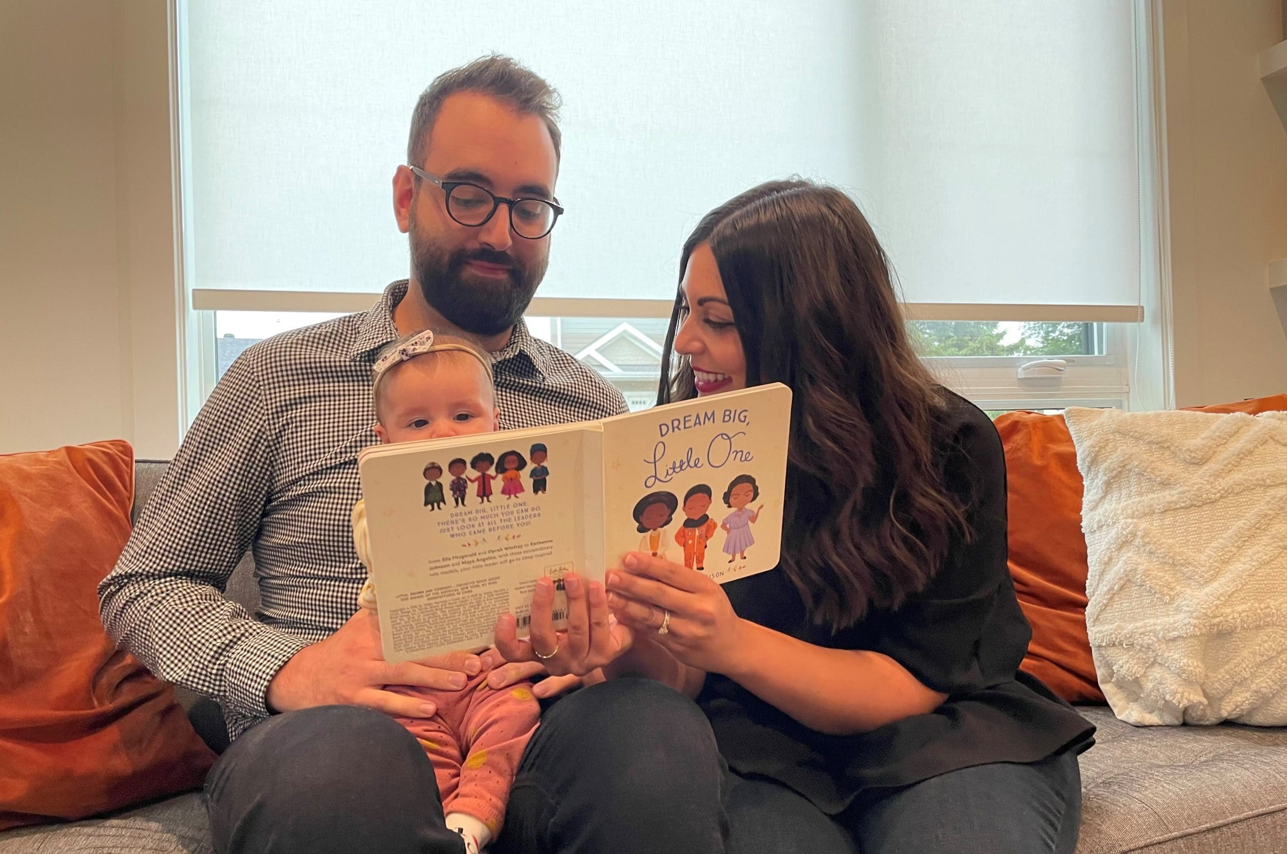 The Afonso family sit on a couch while reading a book to their baby