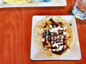 A mole poblano chicken taco on a white plate