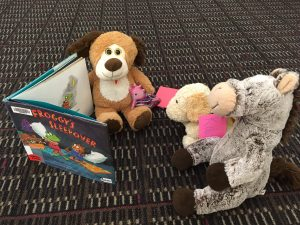 Stuffed animals read the book Froggy's Sleepover