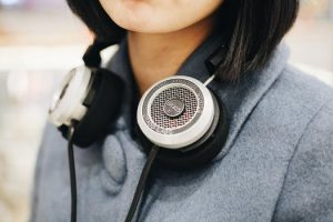 Young woman in a grey sweater with black and white headphones resting around her neck.