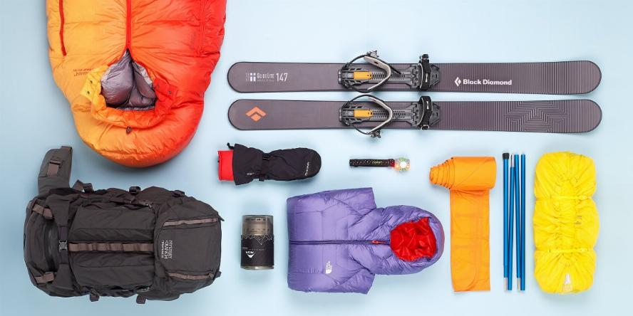 Flatlay of products recommended by Outside magazine for winter camping. Including a backpack, down sleeping bag, skis, insulated jacket, and other items.