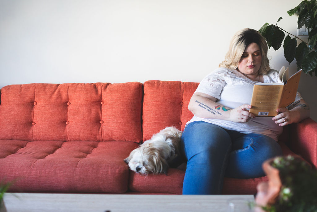 Reading with a dog on a cozy sofa