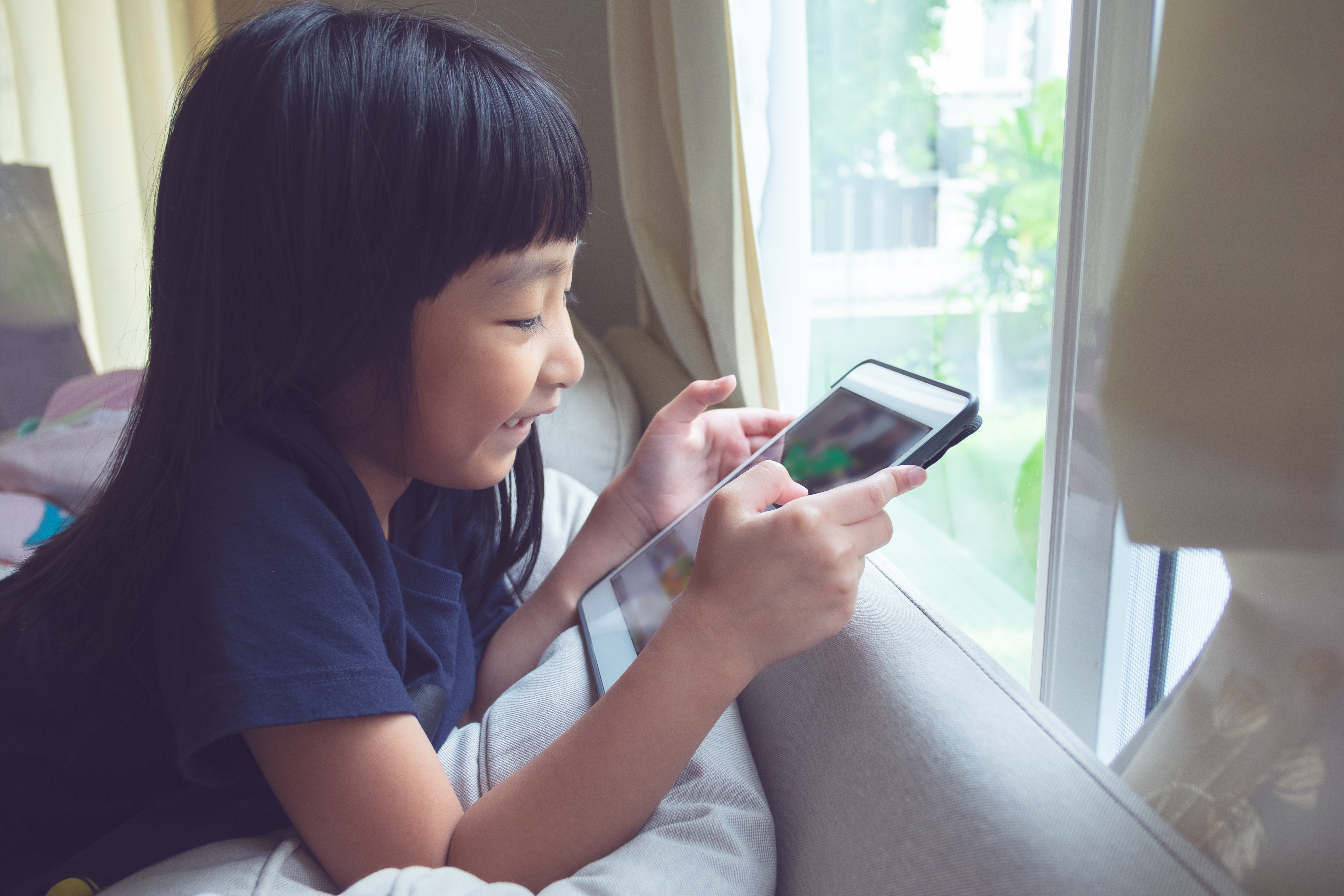 top-section-portrait-of-a-thai-little-girl-sitting-down-at-window-using-a-smart-device-in-her-hand_t20_goZYb8