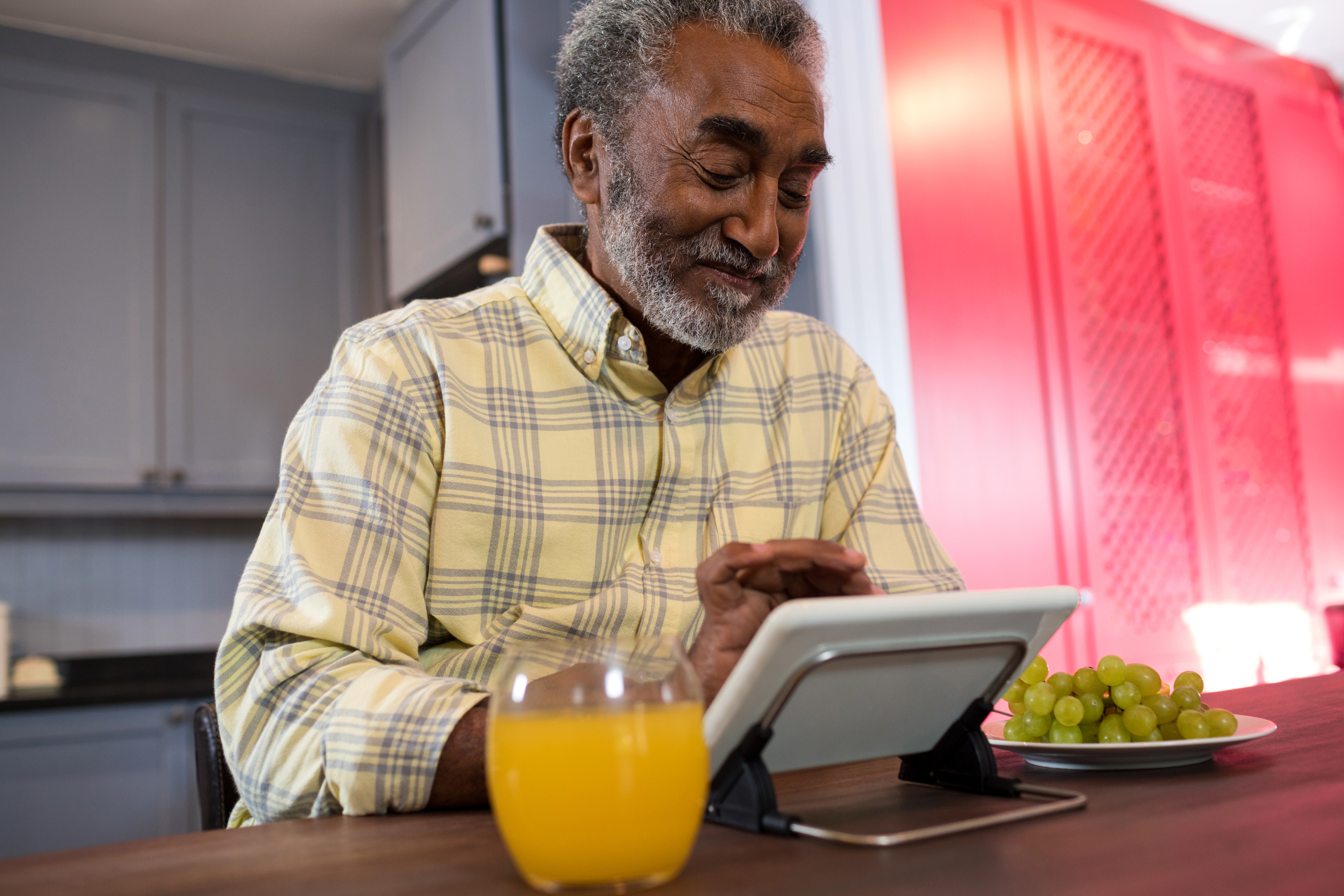 Happy senior man using tablet computer in kitchen