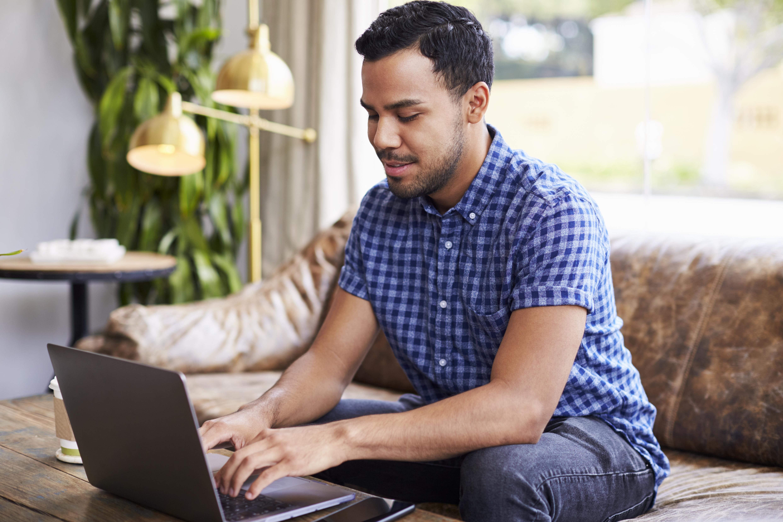Young Hispanic man using laptop