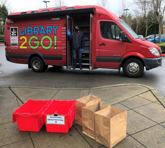 Library staff member wearing gloves and a mask waving from the door of a Library2Go van. A red bin for returns and paper bags of items for checkout are placed several feet away from the van on the sidewalk.