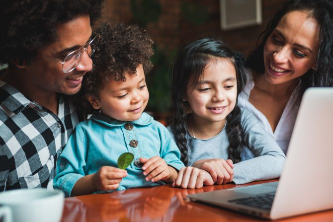 Happy multiethnic family having fun while using laptop together