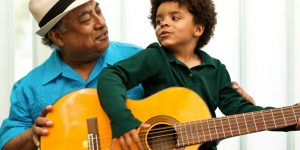Photo of Jose-Luis Orozco with child playing the guitar. Source: Jose-Luis Orozco