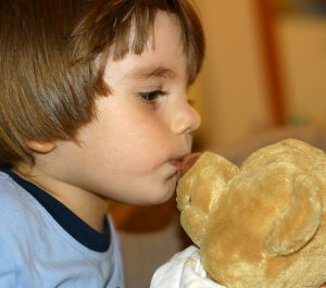 Photo of child kissing his teddy bear. Source: Leonid Mamchenkov, Flickr.