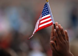 Child with US flag in hand. Source: DVIDSHUB, Wikimedia Commons.