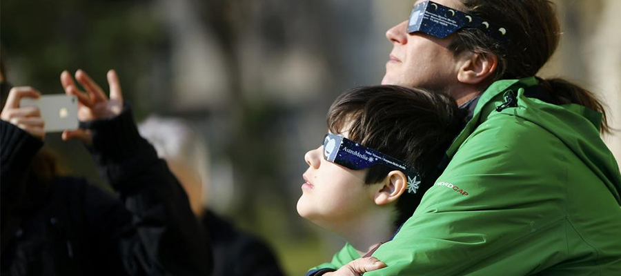 People use protective glasses to observe a partial solar eclipse.