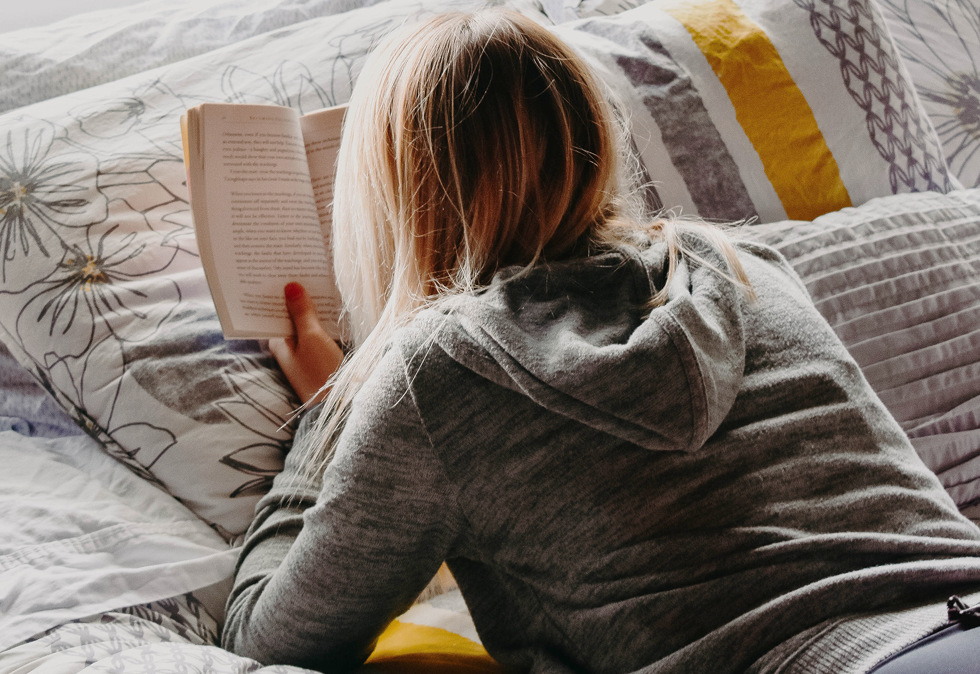 Teen reading book on bed.