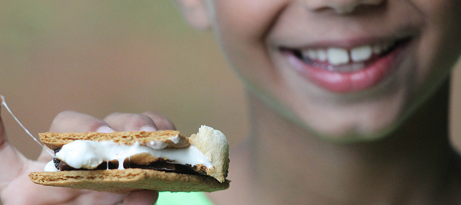 Boy holding s'mores in hand.