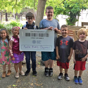 Children posing with giant library card.
