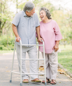 Elderly man, assisted by a walker, walking with wife in the park.
