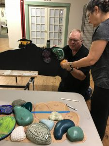 """Tom Quest and Marcia Joffe-Bouska mounting """"river stones"""" to plywood supports for their collaborative exhibition """"Rivers."""""""