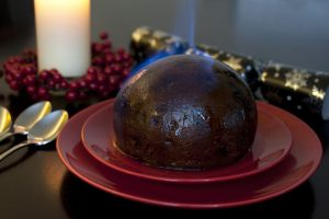 Flaming traditional fruity Christmas pudding set alight with brandy before serving on a festive Xmas table for dinner