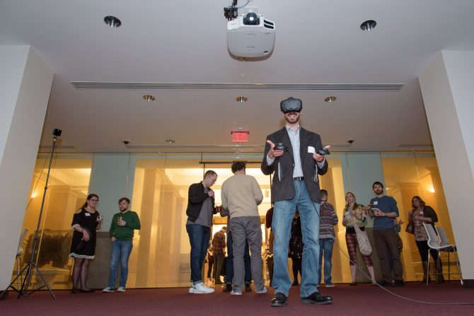 A patron is pictured wearing a VR headset as a crowd of onlookers watches