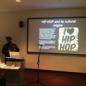 """Alonzo Lee in front of a slide that says """"I heart Hip Hop"""""""
