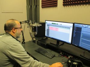 Image of a person in front of a microphone and a computer in the Recording Room