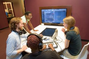 A group of four patrons works on a FL Studio project at one of the Pods. The Recording Room is shown in the background.