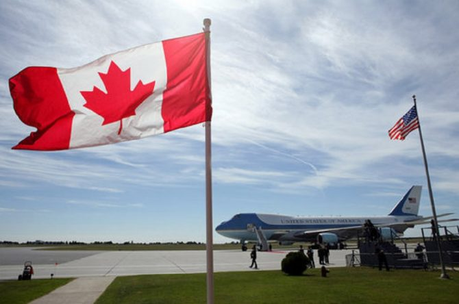 Air Force One, framed between American and Canadian flags (Archives.gov photo)