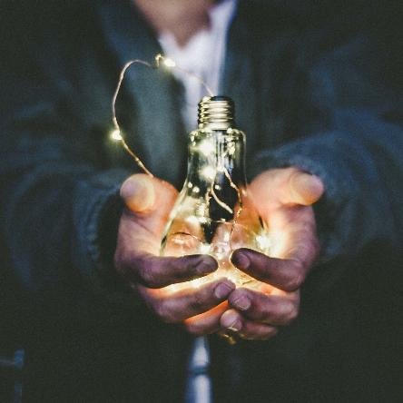 Photo of man's hands holding a lit lightbulb