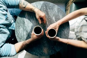 Image of two people at a table with cups of coffee