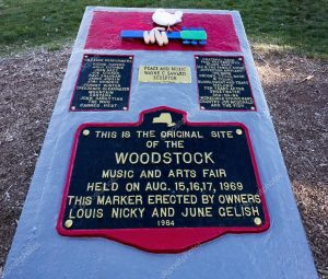 "Photo of a plaque commemorating the location of Woodstock. Text of the plaque: ""This is the original site of the Woodstock Music and Arts Fair held on August 15, 16, 17, 1969. This marker erected by owners Louis Nicky and June Gelish"""