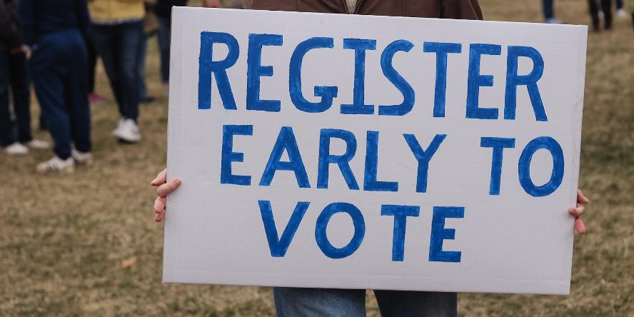 man holding a register early to vote sign