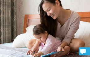 Mother and Baby looking at a book on a bed