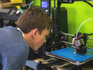 teen looking at 3d printer