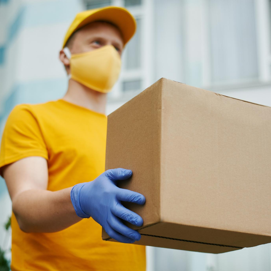 man with facemask carrying a box