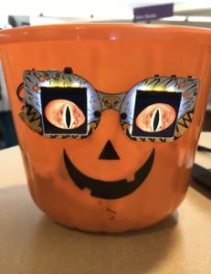 """Hallowing Treat Eyes"", Materials: Adafruit Monster Mask, Lithium Ion Polymer Battery, Pumpkin Treat Bucket"